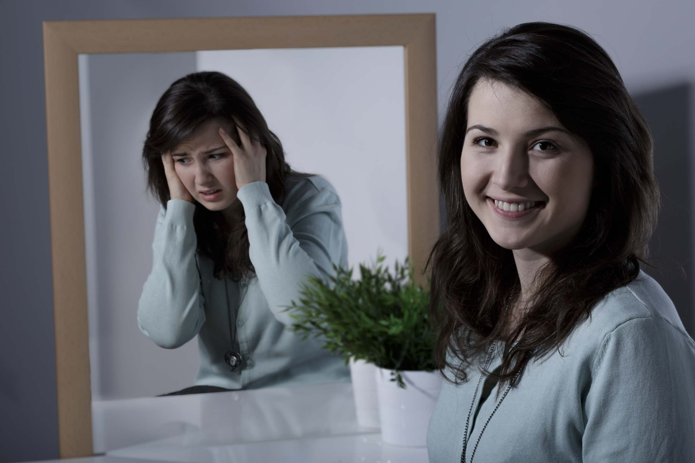 Girl with bipolar disorder looking in the mirror